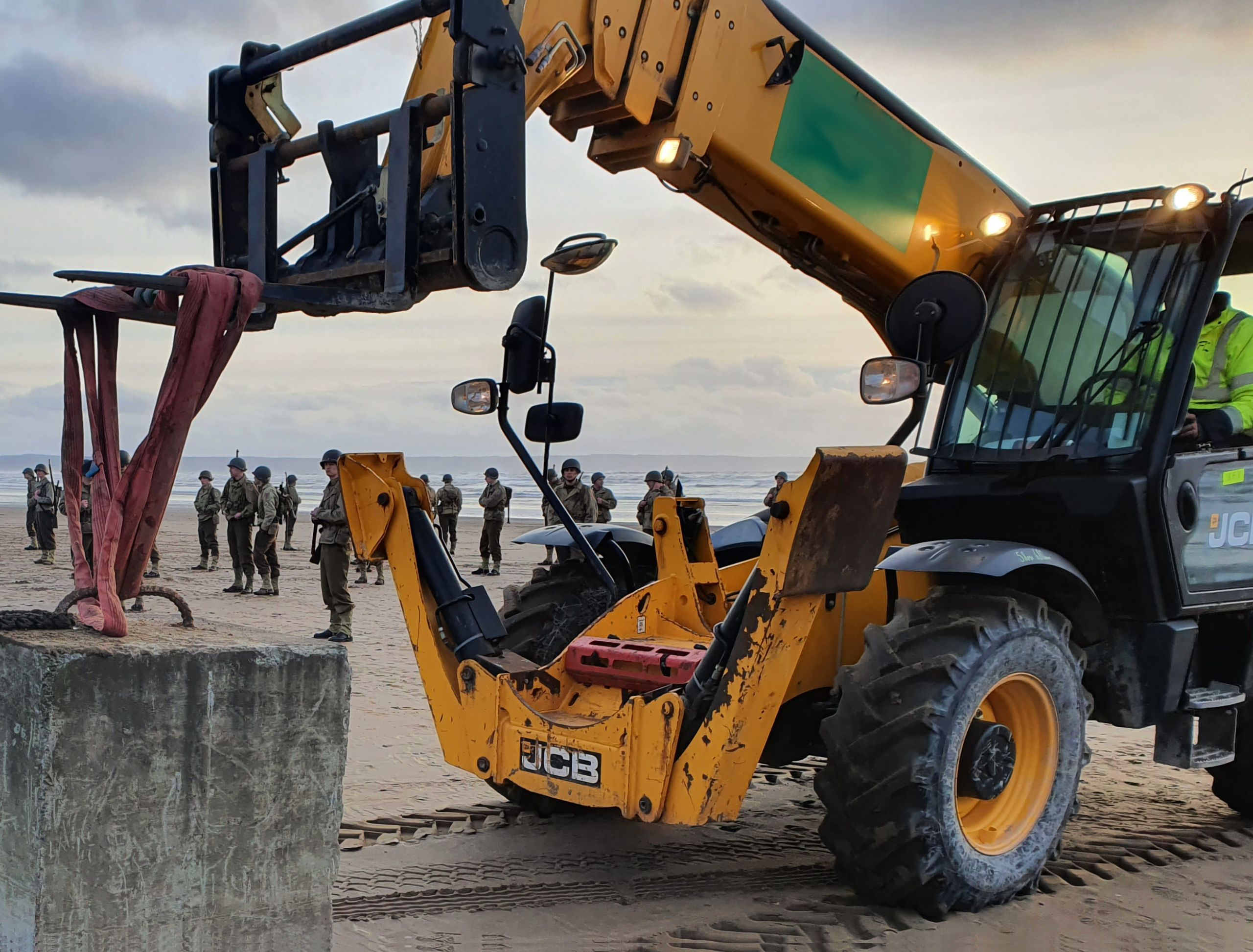 Telehandler moving a mooring block on the beach during filming